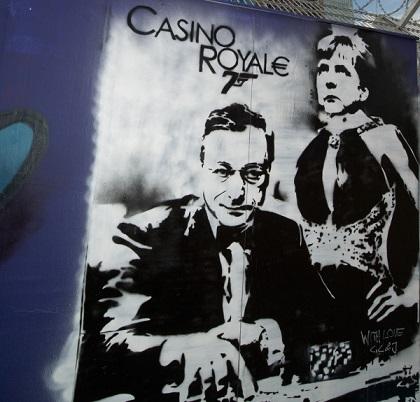 Ein Graffitti am Bauzaun des Neubaus der Europäischen Zentralbank (EZB) zeigt am 10.05.2013 EZB-Chef Mario Draghi und die deutsche Bundeskanzlerin Angela Merkel in Frankfurt am Main. Dabei erinnert der Titel des Kunstwerkes in seiner Gestaltung an einen James-Bond-Film. Foto: Boris Roessler/dpa +++(c) dpa - Bildfunk+++